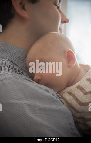 Baby boy sleeping on father's shoulder, close up - Stock Photo