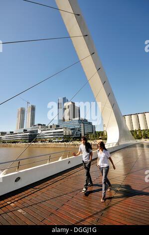Tourists walking on a modern suspension bridge, Puente de la Mujer bridge, Women's Bridge, in the old harbor of - Stock Photo