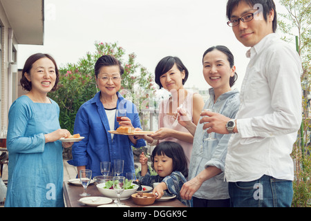 Three generation family eating outdoors, portrait - Stock Photo