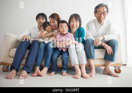 Three generation family sitting on sofa, portrait - Stock Photo