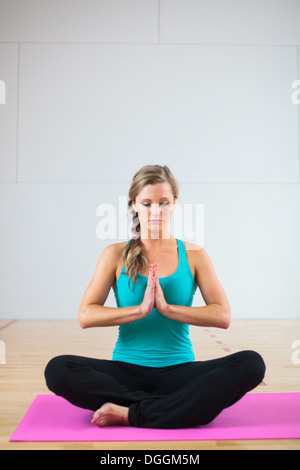 Young woman on yoga mat in lotus position - Stock Photo