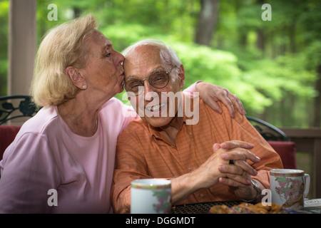 Senior woman kissing man, smiling - Stock Photo
