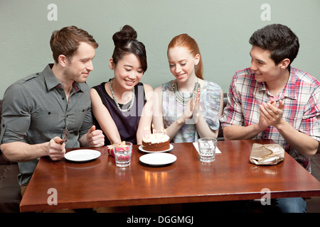 Four friends celebrating birthday in restaurant - Stock Photo