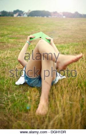 Teen girl lying in field, reading book - Stock Photo
