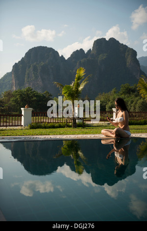 Woman sitting on poolside, Vang Vieng, Laos - Stock Photo