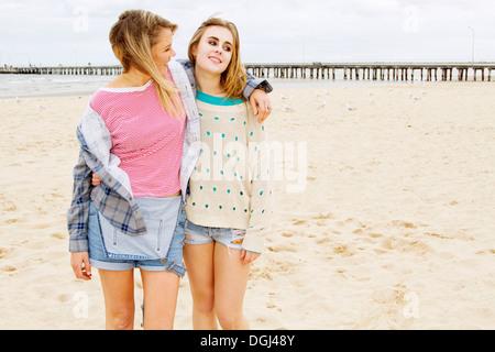 Girlfriends standing on beach with arm around - Stock Photo