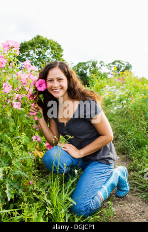 Portrait of young woman holding pink flower in allotment - Stock Photo