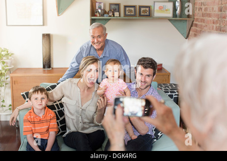 Person taking photograph of three generation family - Stock Photo