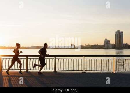 Jogging couple running on riverside early morning - Stock Photo