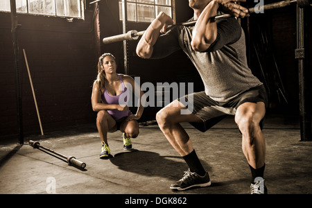 Young man and personal trainer working out in gym - Stock Photo