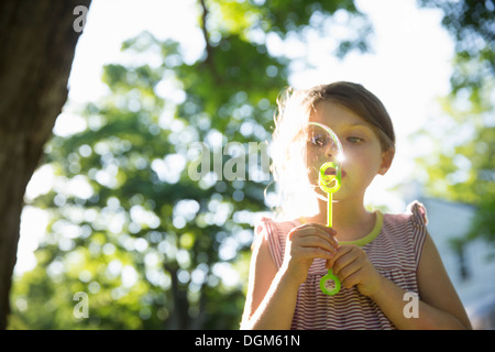 Outdoors in summer. A young girl blowing bubbles in the air under the branches of a large tree. - Stock Photo