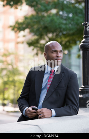 Business people. A man in a suit leaning on a balustrade under a lamppost. Waiting. - Stock Photo