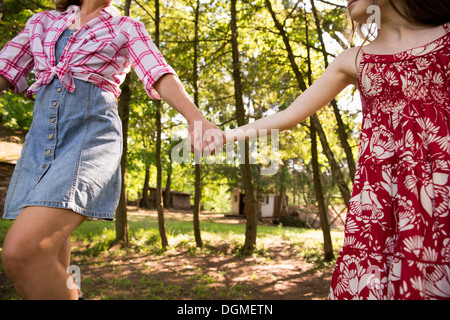 A woman and a young girl holding hands and running along under the trees. - Stock Photo