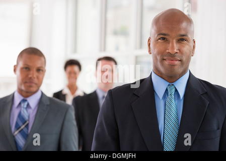 Business people. A team of people, a department or company. Three men and one woman. - Stock Photo