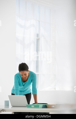 Business. A woman leaning over a desk using a laptop computer. - Stock Photo
