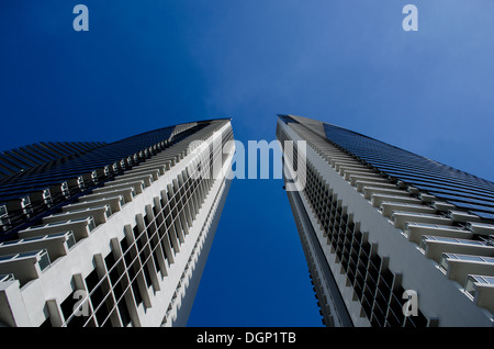 Two skyscrapers from below with blue sky in the background - Stock Photo