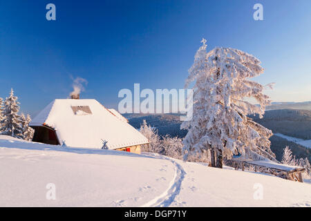 Snow-covered cottage on the Belchen summit with a view to the Feldberg, Black Forest, Baden-Wuerttemberg - Stock Photo