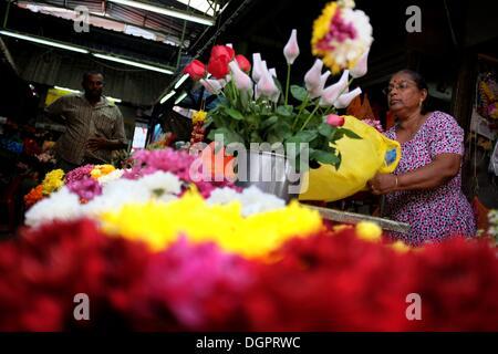 Kuala Lumpur, Malaysia. 23rd Oct, 2013. A women prepare her flower stall at Jalan Tunku Abdul Ramhan on October - Stock Photo