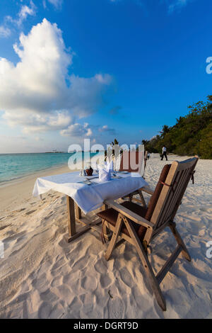 A table laid for dinner standing on the beach, Paradise Island at the back, Lankanfinolhu, North Male Atoll - Stockfoto