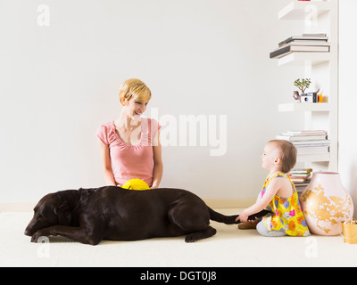 Mother with baby daughter (12-17 months) playing with dog - Stock Photo