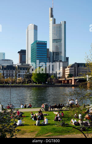 People at the riverside of the Main River, Schaumain Kai, Museumsufer, in front of the skyline of the office and - Stock Photo