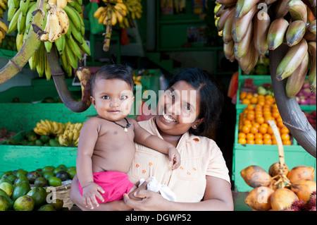 Female vendor holding her baby, market stall selling fruit and vegetables, Bentota, Aluthgama, Sri Lanka - Stockfoto