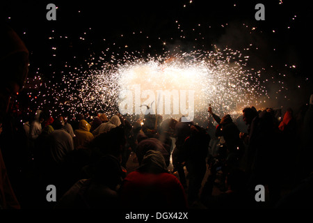 People dance surrounded by fire and pyrotechnics during a traditional fire run in the island of Mallorca, Spain - Stock Photo