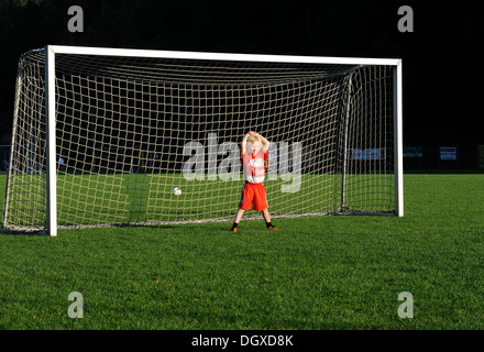 Five-year-old boy wearing a FC Bayern Munich soccer dress, boredly standing in a soccer goal - Stock Photo