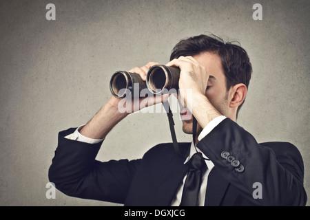 Young businessman watching through binoculars - Stock Photo