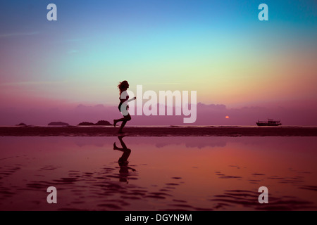 wellbeing or sport background, woman silhouette on the beach - Stock Photo