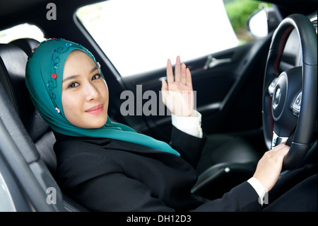 head scarf girl wave hand in her car - Stockfoto