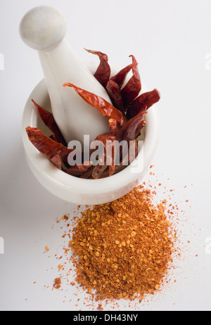 Red chili peppers in a mortar with paprika - Stock Photo
