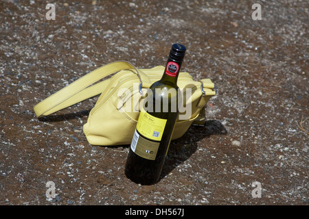 A yellow handbag and a partially empty bottle of wine left on a pavement. - Stock Photo