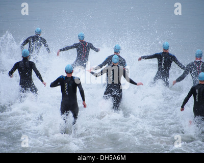 Triathletes enter the sea at the start of the Portsmouth 2013 triathlon. - Stock Photo