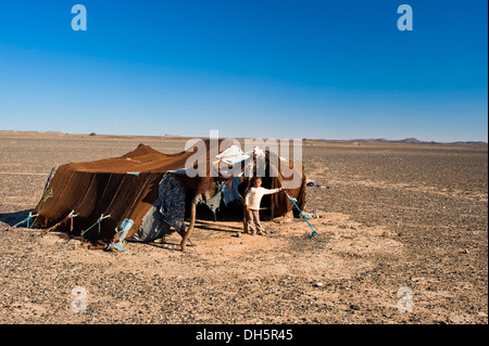 Young boy standing in front of the tent of his nomadic family, stone desert, hamada, Erg Chebbi, Southern Morocco, - Stockfoto