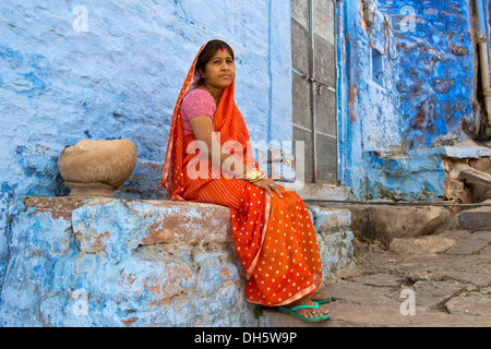 Elderly woman wearing a red sari sitting on a ledge of a blue painted residential building, Brahmpuri, Jodhpur, - Stockfoto