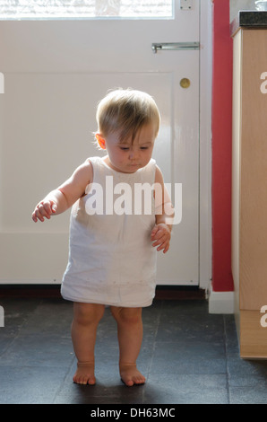 Nine month old girl learning to stand and walk on kitchen floor.  England, UK. - Stock Photo