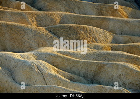 View from Zabriskie Point over eroded rock formations discoloured by minerals, evening light, Death Valley National - Stock Photo
