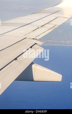 View of a wing from airplane illuminator - Stock Photo