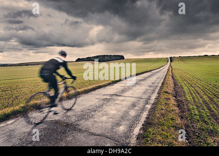Lone Cyclist in UK Countryside - Stock Photo