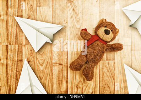 Cute bear toy on laminated wooden floor with paper origami planes - Stock Photo