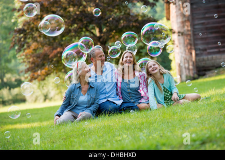 A family sitting on the grass outside a bar, blowing bubbles and laughing. - Stock Photo