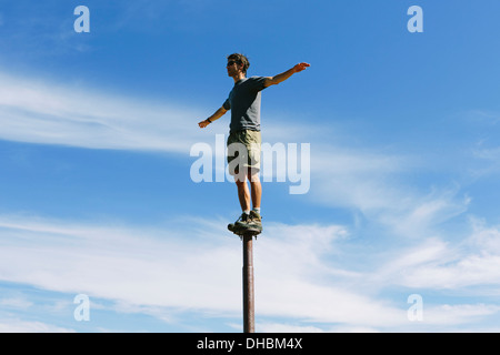 Man standing balancing on metal post looking towards expansive sky on Surprise Mountain Alpine Lakes Wilderness - Stock Photo