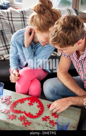 Couple doing heart shaped jigsaw - Stockfoto
