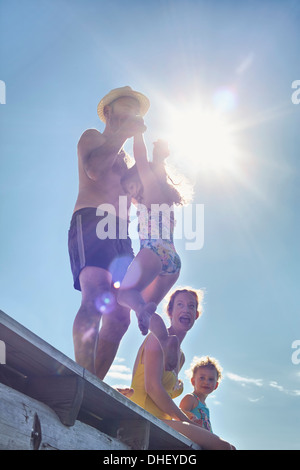 Young family playing on pier, Utvalnas, Gavle, Sweden - Stock Photo