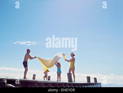 Young family having fun on pier, Utvalnas, Gavle, Sweden - Stock Photo