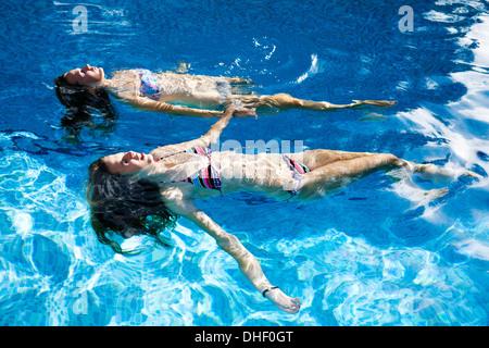 Two teenage girls floating in swimming pool - Stock Photo
