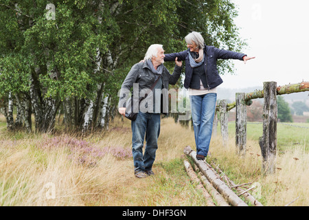 Senior couple, woman balancing on logs - Stock Photo