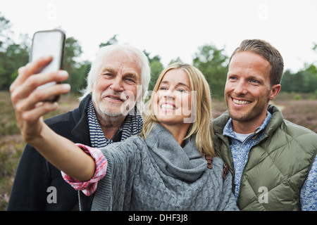 Mid adult woman taking photograph with camera phone - Stock Photo