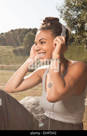 Young woman listening to music in park - Stock Photo
